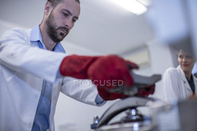 Man working in lab wearing protective clothing — Stock Photo