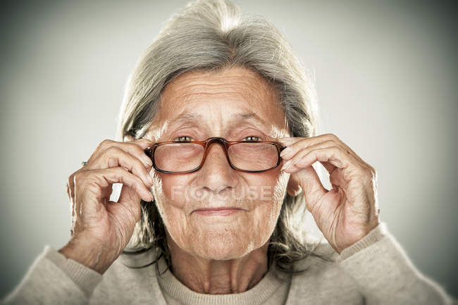 Portrait of smiling senior woman holding glasses and looking at camera — Stock Photo