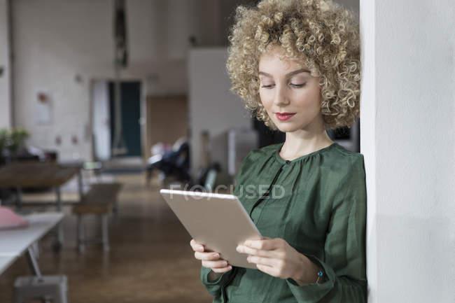 Femme utilisant une tablette numérique au bureau — Photo de stock