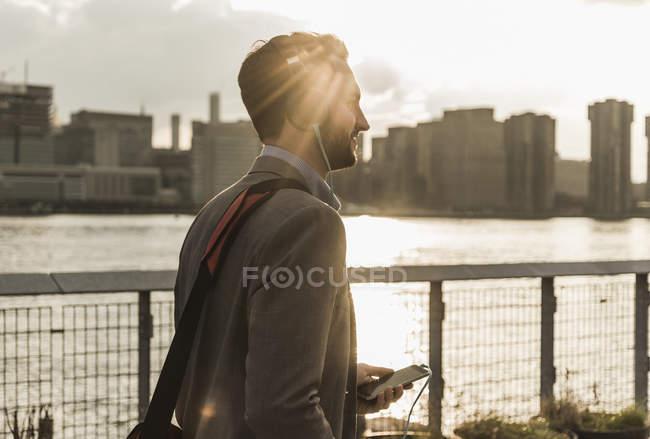 Jeune homme avec casque et téléphone cellulaire à East River, New York, USA — Photo de stock