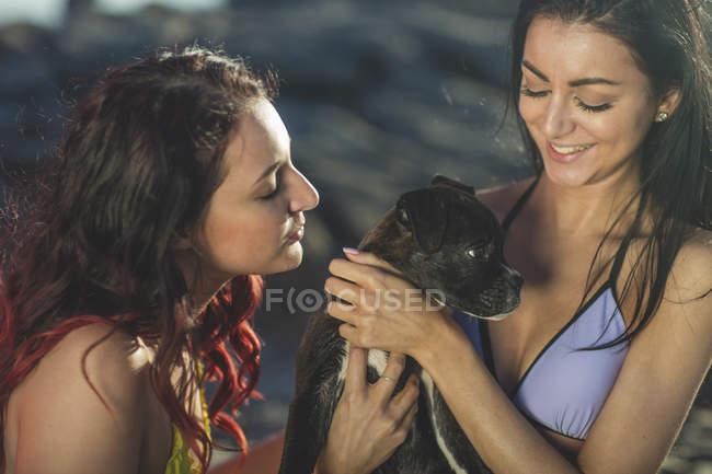 Две молодые женщины с собакой на пляже — стоковое фото