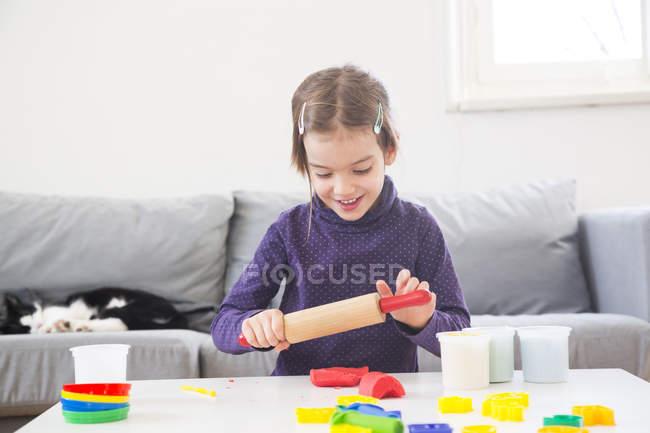 Petite fille roulant pâte à modeler à la maison — Photo de stock