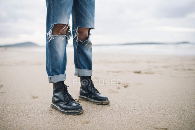 Female legs wearing boots and torn jeans on the beach — Stock Photo