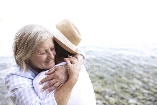 Активная милая пожилая пара, обнимающаяся на пляже — стоковое фото