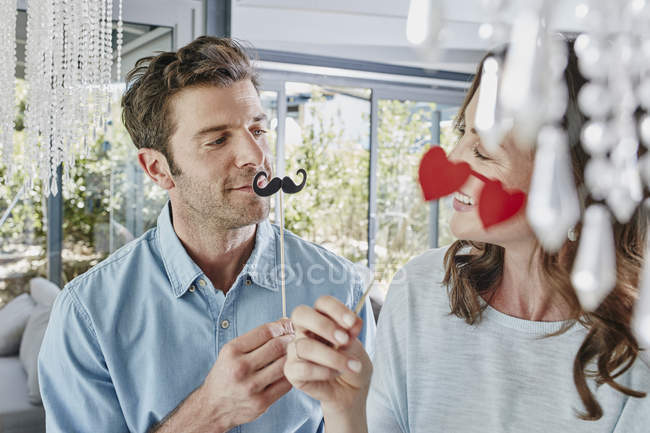 Couple with paper moustache and heart-shape mask — Stock Photo
