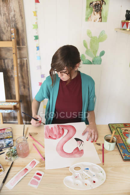 Woman painting aquarelle of a flamingo on desk in her studio — Stock Photo