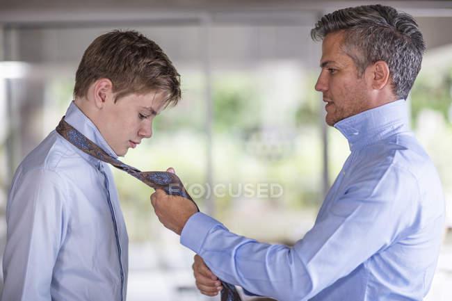 Vater hilft indem Befestigung Söhne Krawatte — Stockfoto