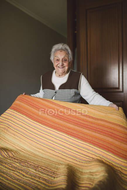 Smiling senior woman making bed at home — Stock Photo