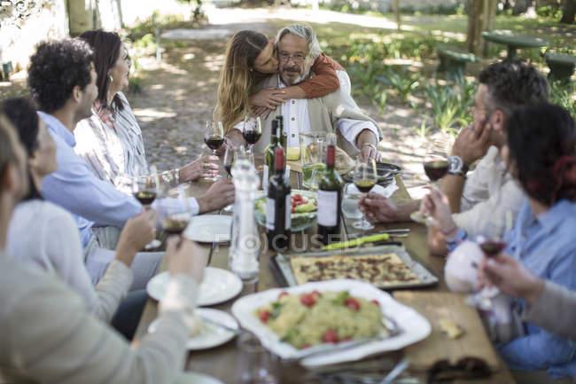 Père de 1.prix fille assis comme des amis et la famille déclenche un toast avec verres à vin en dehors des repas jardin — Photo de stock