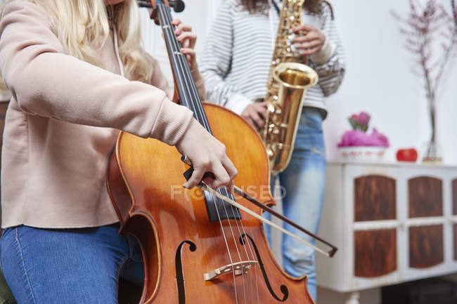 Two girls playing cello and saxophone together — Stock Photo