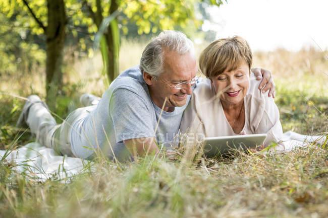 Pareja mayor tumbada en el jardín sobre manta con tableta digital - foto de stock