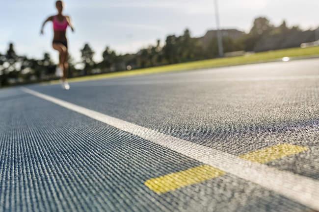 Затуманенное спринтер женщина работает в Ипподром, фокус на переднем плане — стоковое фото