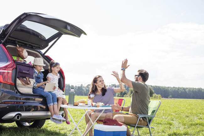Happy family on a road trip taking a break at road side — Stock Photo