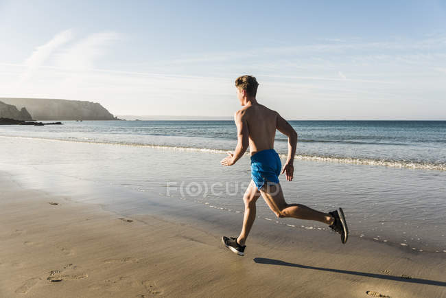 Young man running on the beach, france, crozon peninsula — Stock Photo