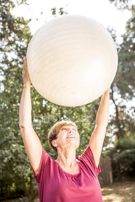Donna anziana che si allena con palla fitness all'aperto — Foto stock