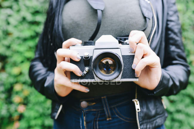 Woman's hands holding analogue camera, close-up — Stock Photo