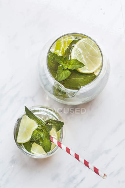 Glass and carafe of detox water with mint and limes — Stock Photo