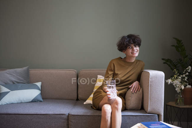 Portrait of smiling young woman with glass of water sitting on couch at home — Stock Photo