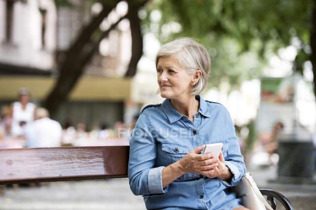 Alegre adulto mayor mujer usando teléfono inteligente contra fondo borroso - foto de stock