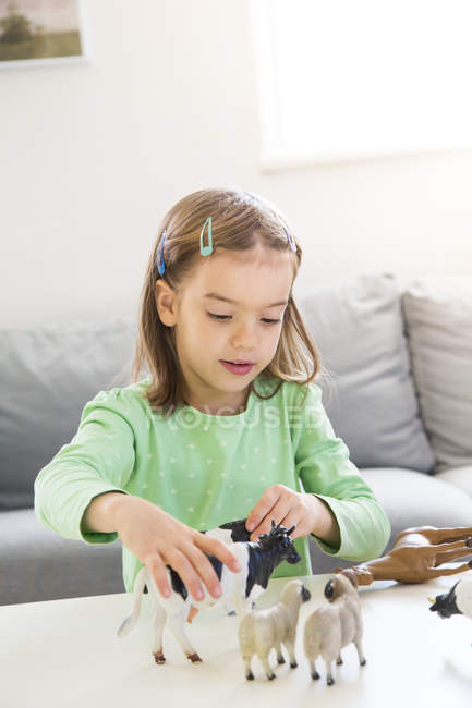 Little girl playing with animal figurines at home — Stock Photo
