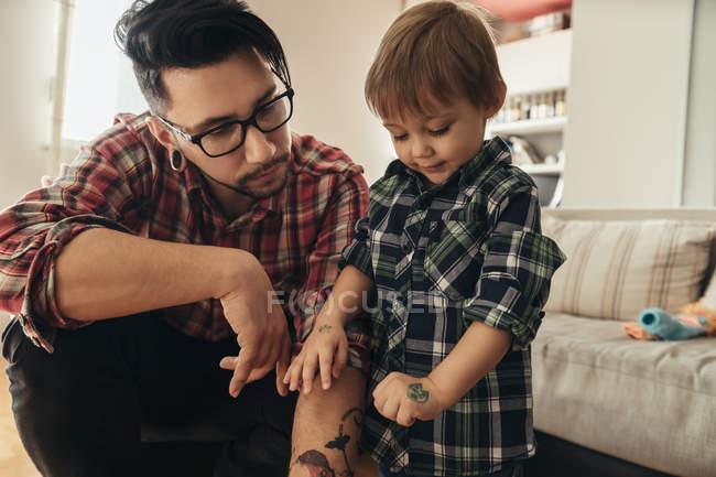 Orgulloso hijo mostrando pintado tatuaje en mano - foto de stock