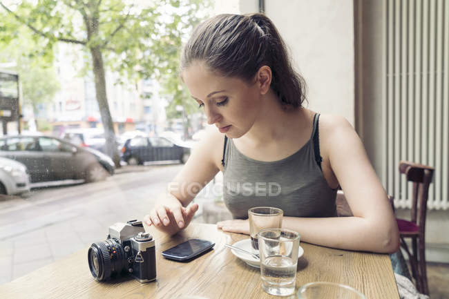 Young woman in a cafe with camera checking cell phone — Stock Photo