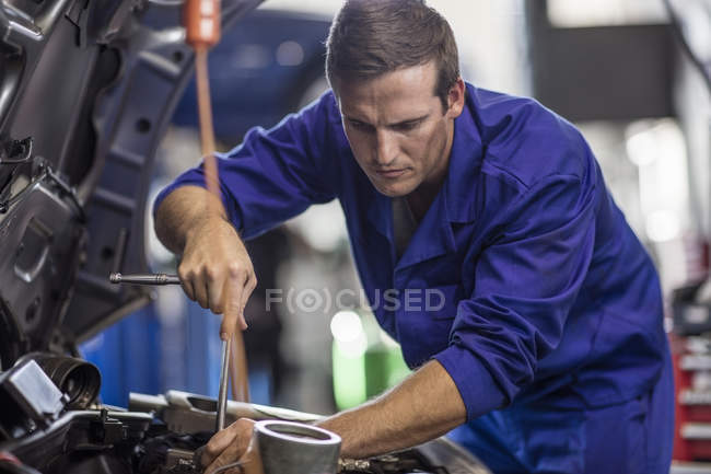 Car mechanic in a workshop repairing car — Stock Photo
