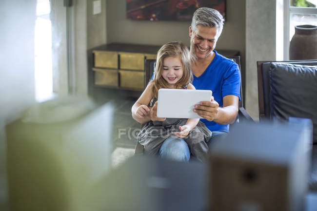 Father and daughter having fun looking at digital tablet — Stock Photo