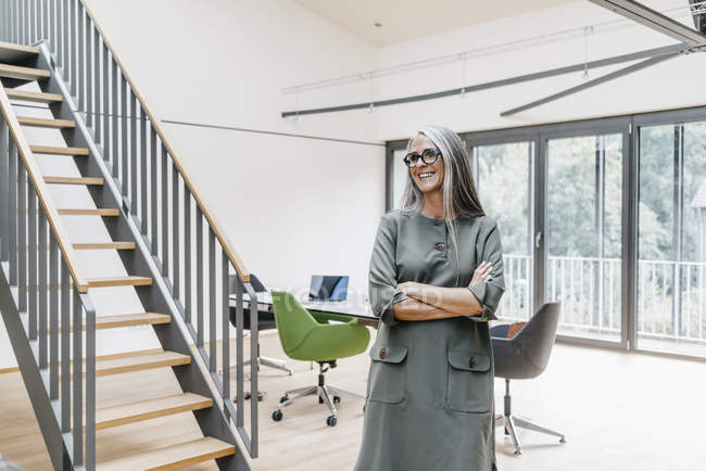 Smiling woman with long grey hair standing in office — Stock Photo