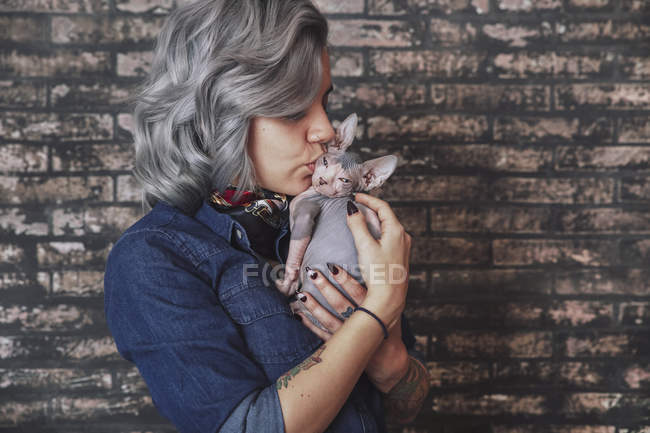 Young woman kissing Sphynx cat — Stock Photo