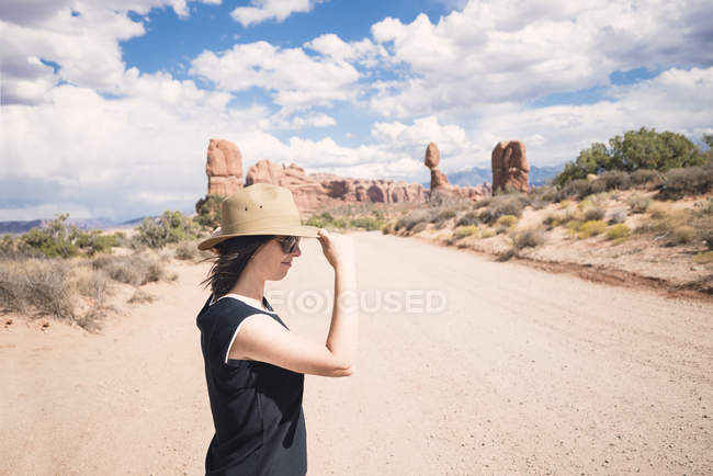 USA, Utah, Arches National Park, woman with straw hat  on dirt track to the Windows Section — Stock Photo