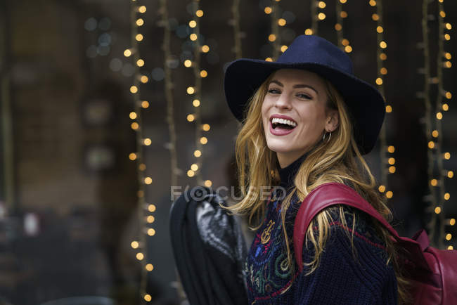 Portrait of laughing young woman wearing blue hat — Stock Photo