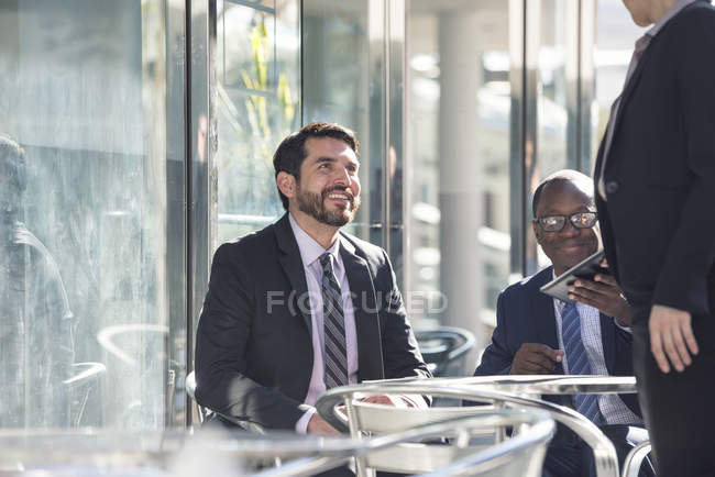 Smiling business people meeting at outdoor cafe — Stock Photo