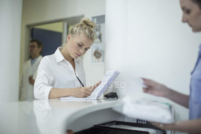 Woman writing in book at reception in clinic — Stock Photo