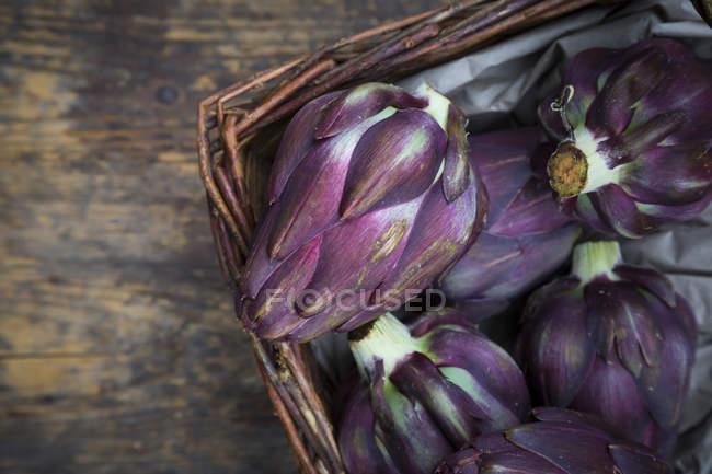 Basket of purple organic artichokes — Stock Photo