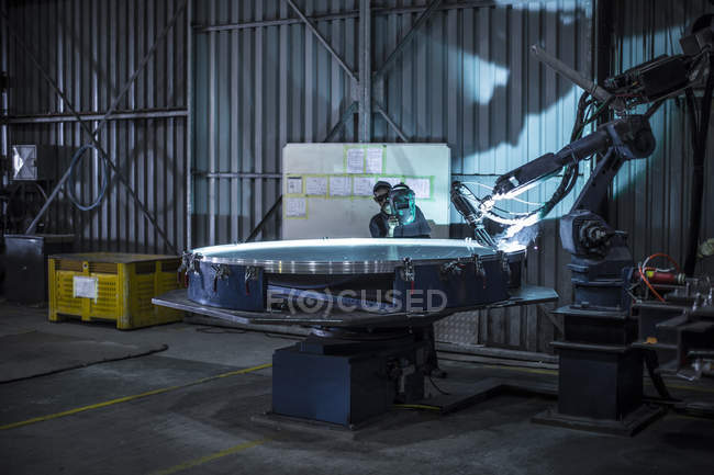 Welder standing behind industrial lathe cutting steel in factory — Stock Photo