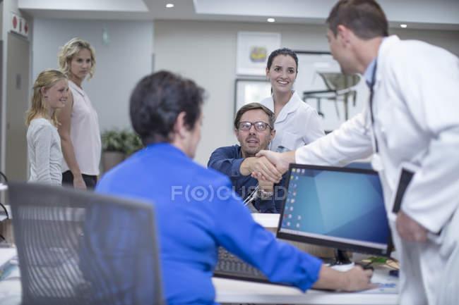 Patient en fauteuil roulant saluant médecin à la réception à l'hôpital — Photo de stock