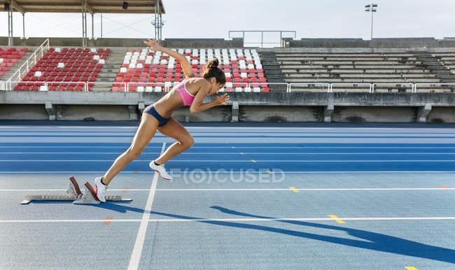 Вид сбоку спринтер женщины, начиная гонку — стоковое фото