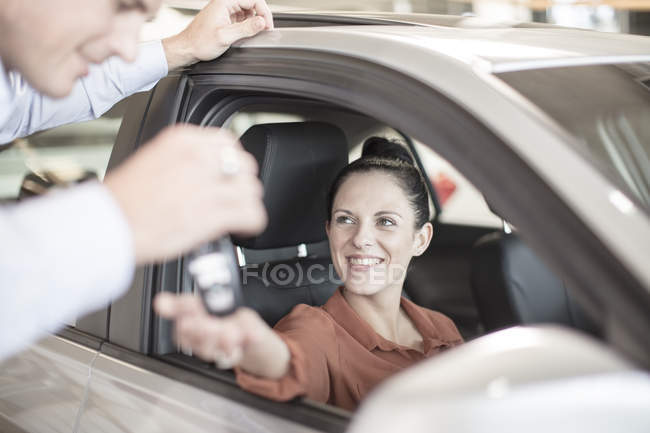 Car dealer giving key to woman sitting in car — Stock Photo