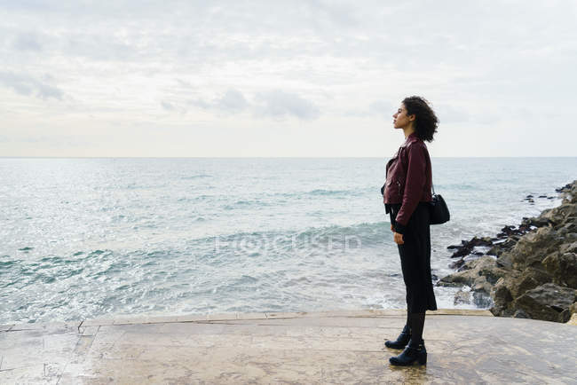 Woman standing in front of the sea and looking at distance — Stock Photo