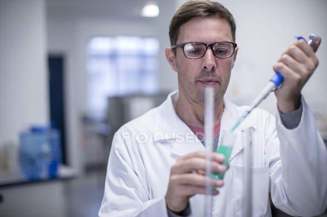 Caucasian male scientist pipetting in lab — Stock Photo