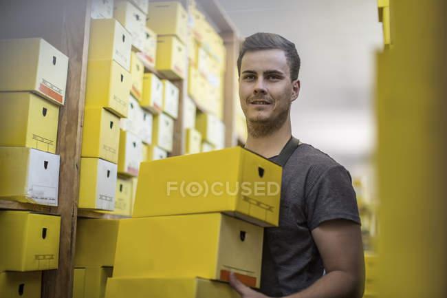 Jeune homme dans un entrepôt portant des boîtes à chaussures — Photo de stock