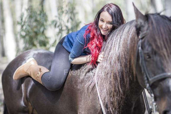 Улыбающаяся молодая женщина лежит на лошади — стоковое фото