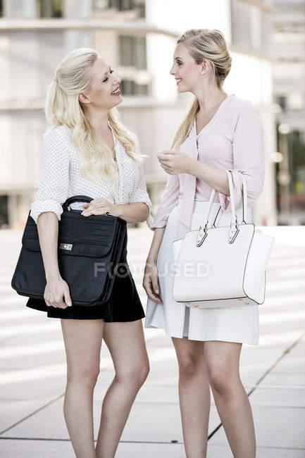 Due donne d'affari alla moda con borse che parlano — Foto stock