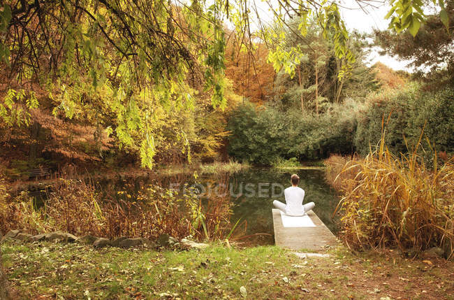 Man sitting on a jetty at a pond in autumn — Stock Photo