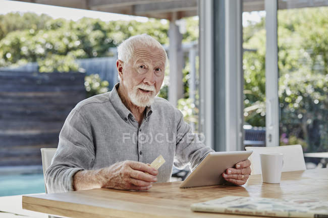 Senior man sitting on terrace, doing online payment with credit card — Stock Photo