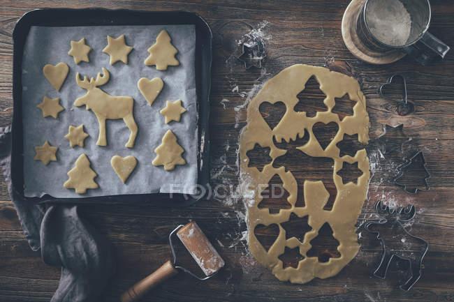 Рождественские хлебобулочных изделий, печенья на металлические подносы и формы тесто вид сверху — стоковое фото