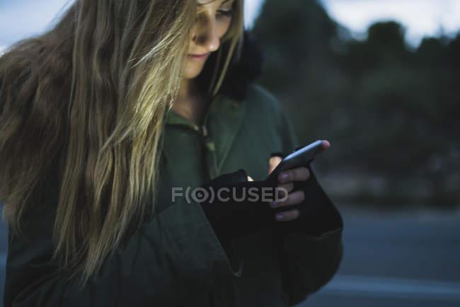 Улыбающаяся молодая женщина отправляет сообщения на открытом воздухе вечером — стоковое фото