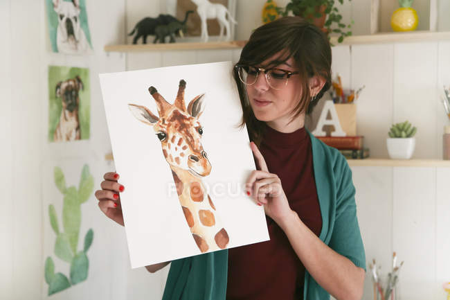 Portrait of artist showing her aquarelle of a giraffe — Stock Photo