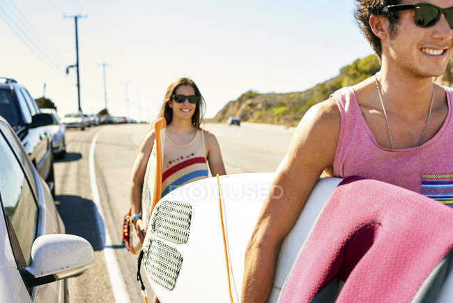 Smiling young couple carrying surfboards on coastal road — Stock Photo